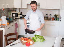 Man cooking at home and preparing food. Good Stock Photo