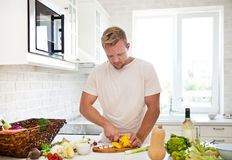 Man cooking at home preparing salad in kitchen Royalty Free Stock Images