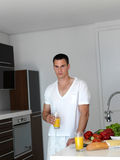 Man cooking at home preparing salad in kitchen Stock Images