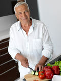 Man cooking at home preparing salad in kitchen Stock Photography
