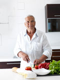 Man cooking at home preparing salad in kitchen Royalty Free Stock Photography