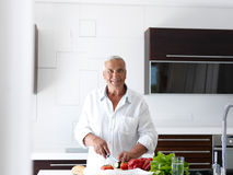 Man cooking at home preparing salad in kitchen Royalty Free Stock Photo