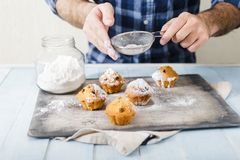 Man cooking homemade cupcakes with raisins and powdered sugar. Male hands sprinkle powdered sugar homemade cupcakes royalty free stock photo