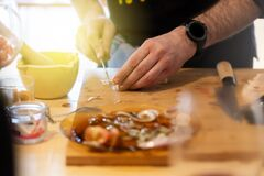 Man Cooking In A Home Kitchen, He Peels Garlic Royalty Free Stock Image
