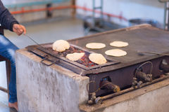 Man cooking Indian flat bread, called chapati Royalty Free Stock Photos