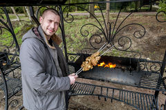 Man cooking kebabs on the grill. Outdoors in the countryside Stock Photo
