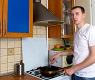 Man cooking at the kitchen. Adult man cooking at the kitchen alone Royalty Free Stock Photos