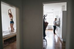 Man cooking in kitchen while happy girlfriend. Jumping on bed in bedroom stock image