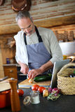 Man cooking in kitchen with help of tablet Royalty Free Stock Image