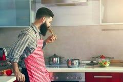 Man cooking at kitchen sampling dish Royalty Free Stock Photos