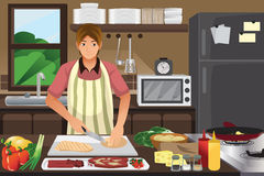 Man cooking in the kitchen Stock Images