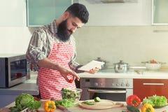 Man cooking making vegetable salad with digital tablet Stock Image