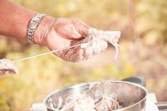 Man cooking marinated shashlik, meat grilling on metal skewer, c Royalty Free Stock Images