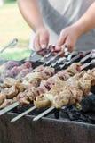 Man cooking marinated shashlik or shish kebab, chiken meat grilling on metal skewer, close up. Selective focus Stock Photo