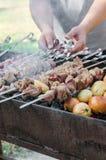 Man cooking marinated shashlik or shish kebab, chiken meat grilling on metal skewer, close up. Selective focus. Man cooking marinated shashlik or shish kebab Stock Images