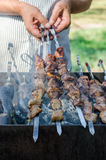 Man cooking marinated shashlik or shish kebab, chiken meat grilling on metal skewer, close up. Selective focus Royalty Free Stock Photo