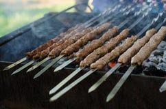 Man cooking marinated shashlik or shish kebab, chiken meat grilling on metal skewer, close up. Selective focus Royalty Free Stock Photos