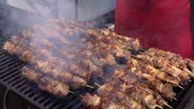 Man cooking meat on barbecue grill for his friends at summer outdoor party. Cooking pork meat on hot charcoal. Closeup stock video footage