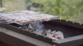 Man cooking meat on the barbecue grill. The man fries meat on fire. stock footage
