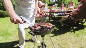 Man cooking meat on barbecue grill at summer party stock video