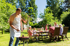 Man cooking meat on barbecue grill at summer party. Food, people and family time concept - men cooking meat on barbecue grill at summer garden party Royalty Free Stock Photos