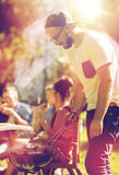 Man cooking meat on barbecue grill at summer party. Leisure, food, people and holidays concept - man cooking meat on barbecue grill for his friends at summer Stock Images
