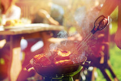 Man cooking meat on barbecue grill at summer party royalty free stock photos