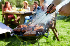 Man cooking meat on barbecue grill at summer party. Leisure, food, people and holidays concept - men cooking meat on barbecue grill for his friends at summer Stock Images