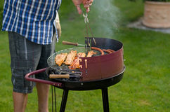 Man cooking meat on a barbecue Royalty Free Stock Images