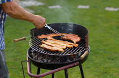 Man cooking meat on a barbecue Stock Photos