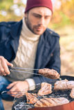 Man cooking meat on charcoal grill Stock Photo