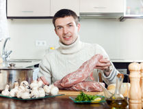 Man cooking  meat with  mushrooms and potatoes. Adding champign Stock Photos