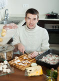Man cooking meat with  mushrooms and potatoes - cutting mushroo Stock Photography