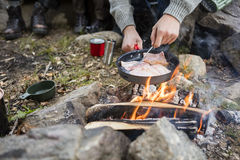 Man Cooking Meat Over Bonfire At Campsite Royalty Free Stock Images