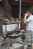 Man cooking meat. Over a wood fire on a rotisserie in Hailuogou China Stock Photo