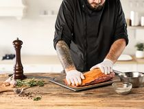 Man cooking meat steak on kitchen. Or home Royalty Free Stock Images