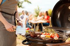 Man cooking meat and vegetables on barbecue grill. Outdoors royalty free stock image