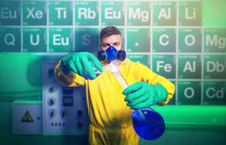 Man cooking meth. Man in protective suit working with tubes while cooking meth royalty free stock images