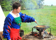 Man cooking on opened fire. Landsknecht man cooking in historical black kitchen with melting kettledrum on opened fire Stock Photography