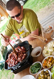 Man cooking outdoors. Cheerful man sitting at a table, cooking outdoors. Portable cooker and asian style vegetable bowls around him Royalty Free Stock Photos