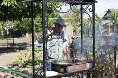 Man cooking pork kebab royalty free stock photography