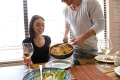 Man cooking and putting food into plate. Girlfriend drinking wine Royalty Free Stock Image