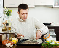 Man cooking raw fish in roasting pan Royalty Free Stock Photos