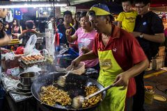 Man cooking rice cake at PJ Pasar Malam stock images