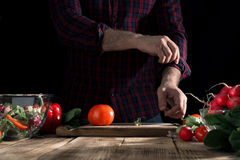 Man cooking salad of fresh vegetables in home kitchen. Preparing healthy food. Man cooking a salad of fresh vegetables on a wooden table in a home kitchen Royalty Free Stock Photo