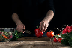 Man cooking salad with fresh vegetables on a wooden table Stock Photography