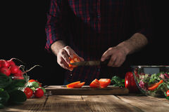 Man cooking salad of fresh vegetables on a wooden table. Man cooking a salad of fresh vegetables on a wooden table. Tasty and healthy food Royalty Free Stock Image