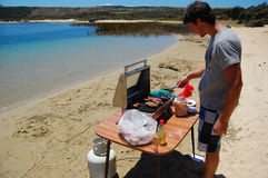 Man cooking sausages at barbeque in beach Royalty Free Stock Images