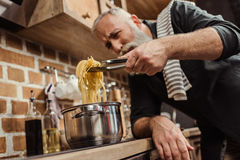 Man cooking spaghetti. Bearded senior man cooking spaghetti in kitchen stock photos