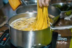 MAN COOKING SPAGHETTI PASTA IN PAN OF BOILING WATER ON COOKER HOB. Chef COOKING SPAGHETTI PASTA IN PAN OF BOILING WATER ON COOKER HOB stock images